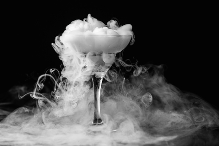 Nahaufnahmeglas mit weißem Nebel am dunklen Hintergrund. Chemische Reaktion von Trockeneis mit Wasser.