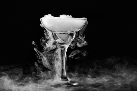 Closeup glass with white fog at dark background. Chemical reaction of dry ice with water. Reklamní fotografie