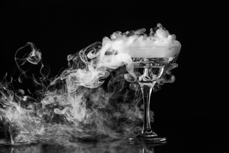 Closeup glass with white fog at dark background. Chemical reaction of dry ice with water. Фото со стока