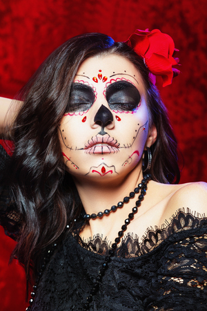 Vertical portrait of traditional mexiacan halloween face art. Brunette lady with rose in hair at red background. Фото со стока
