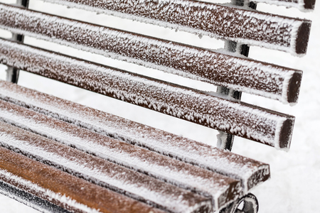 Closeip image of frozen wooden bench covered with snow at white background.