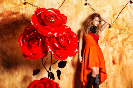 Fashion portrait of young woman in stylish dress standing near big red rose flowers at studio wall background.