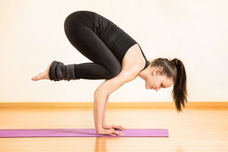 Young woman is practising yoga in bhujapidasana pose at gym background.