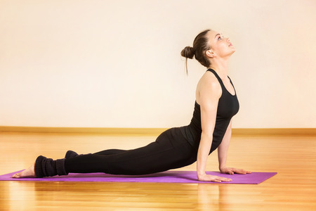 Young woman is training yoga in svanasana pose at gym. Kho ảnh