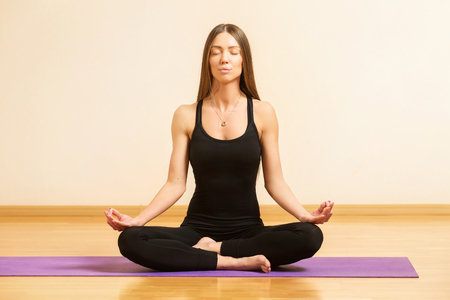 Young woman is practicing yoga and meditating sitting in lotus pose at gym background. Kho ảnh