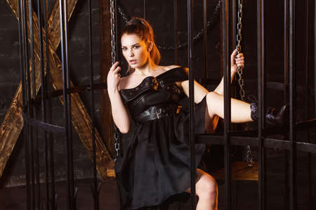 Portrait of young sexy woman in black dress swinging in metal cage.