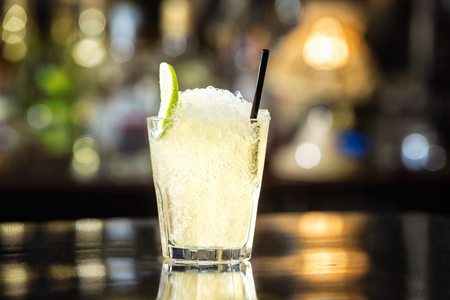 Closeup glass of soda water decorated with lime slice and frappe at bar background. Stock Photo