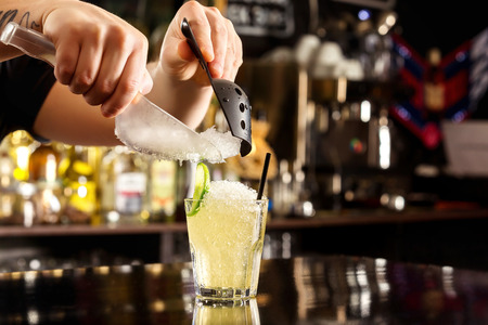 Bartender is decorating cocktail with crushed ice at bar counter background.