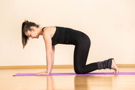 Young woman is practising pilates at gym.