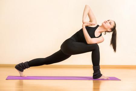 Young woman is practicing anjaneyasana yoga pose at gym background. Stock Photo