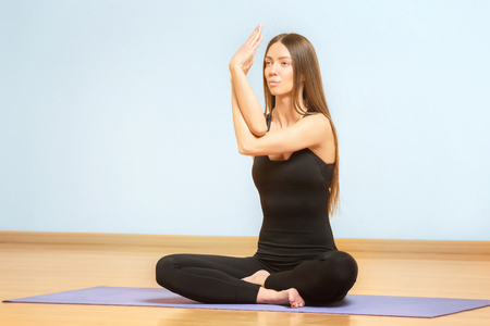 Young beautiful girl is meditating practicing yoga at gym.