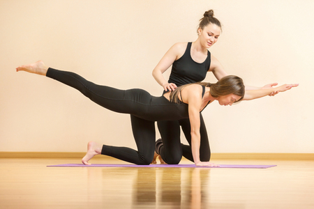 Yoga teacher is helping young woman to make asana poses at gym. Stock Photo