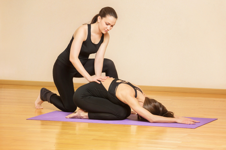 Yoga teacher is helping young woman to make asana pose at gym.