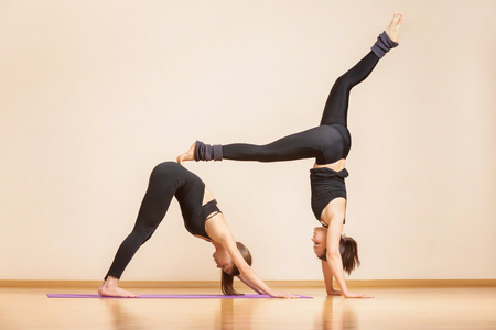 Yoga teacher is showing young woman asana exercise at gym.