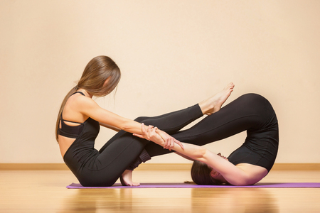 Two young women are practicing yoga at gym. Concept of healthy lifestyle.