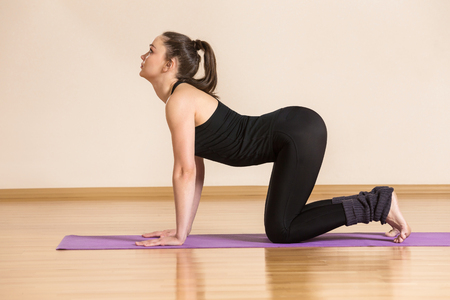 Young woman is making yoga practice at gym background.