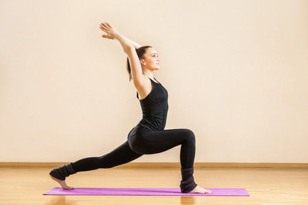 Young woman is practising virabhadrasana known as warrior yoga pose at gym background. Stock Photo