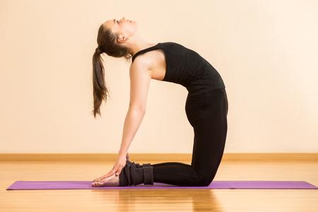 Young female is practicing yoga ushtrasana camel pose at gym background.