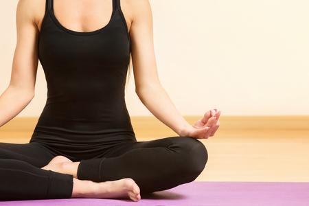 Closeup image of female sitting in lotus pose and meditating at gym.