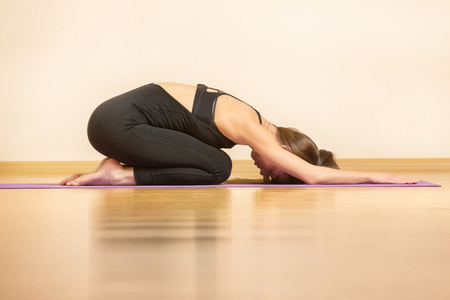 Young woman is training pilates sitting on mat in special pose.