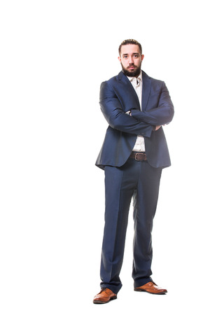 Fashiionable businessman is standing with crossed hands isolated at white background. Vertical image