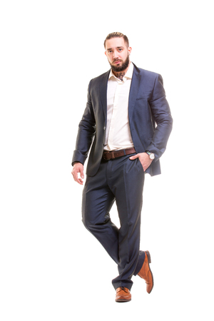 Elegant dressed in suit man with beard is standing isolated at white background. Concept of business success.