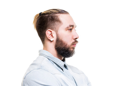 Closeup portrait of young bearded serious caucasian man in shirt isolated at white background.