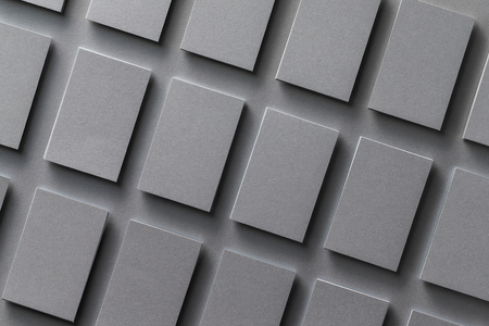 Mockup of black empty business cards stacks arranged in rows at textured background. Brand identity. Stock Photo