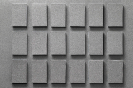 Rows of grey business cards stacks at textured paper background mock-up.