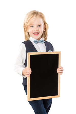 Smart boy in suit with long blond hair is smiling and holding blank blackboard isolated at white background.