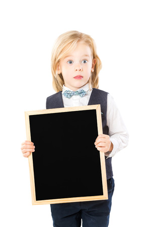 Surprised child in suit is holding blank chalkboard isolated at white background. Stock Photo