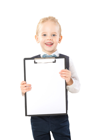 Happy smiling boy in suit is holding folder with blank paper list isolated at white background.