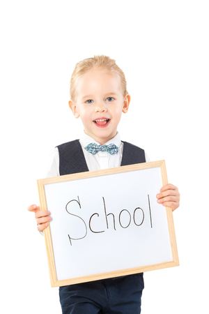 Smiling child in suit is holding board with text School isolated at white background. Stock Photo