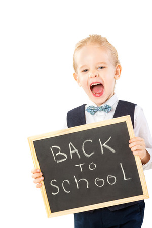 Little boy in suit is holding chalkboard with text Back to school and shouting isolated at white background. Stock Photo