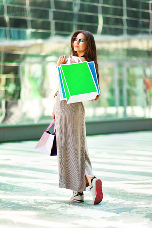 Vertical image of smiling woman standing at mall background and holding bags after shopping.
