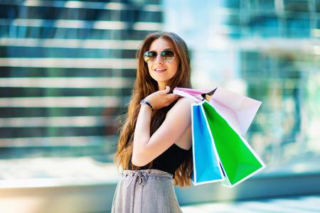 Beautiul stylish girl is holding shopping bags at mall background. Фото со стока