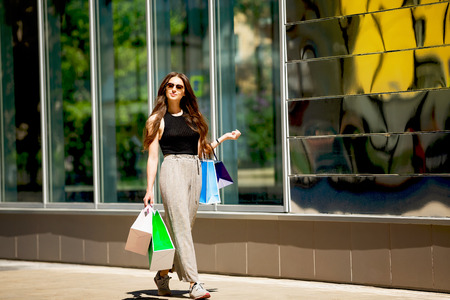 Happy smiling woman is walking along a street with shopping bags at mall background. Фото со стока