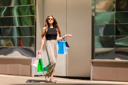 Beautiul stylish girl is walkking along a city street with shopping bags at mall background. Фото со стока