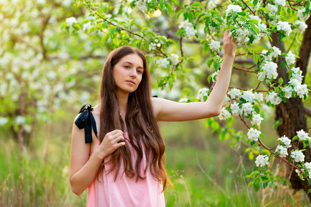 Beautiul young girl in dress is standing at blooming spring apple garden background.