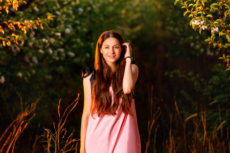 Beautiful girl in pink dress is standing at sunset forest background.