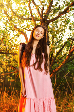 Vertical image of young smiling girl at sunset apple garden background. Фото со стока