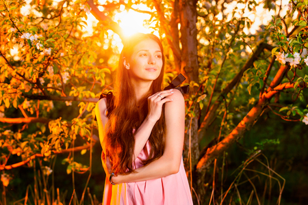 Romantic girl is dreaming at golden sunset ountdoors at blooming garden background.