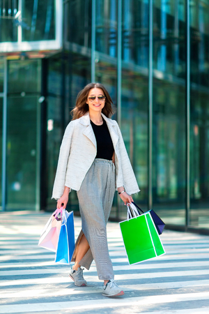 Beautiul stylish girl is walkking along a city street with shopping bags at mall background. Vertical image