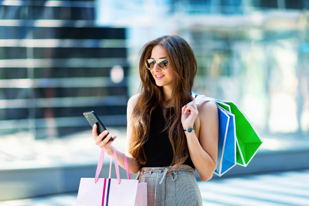Happy smiling woman is standing at mall background, holding bags after shopping and sending sms by mobile phone. Sales concept.