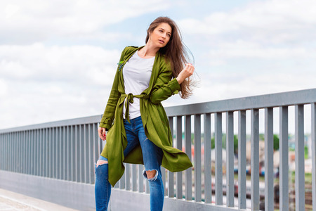 Street fashion portrait of young stylish girl in jeans at urban background.