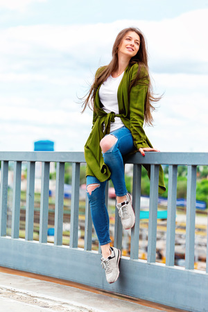 Vertical street fashion portrait of young stylish girl in jeans at urban background.