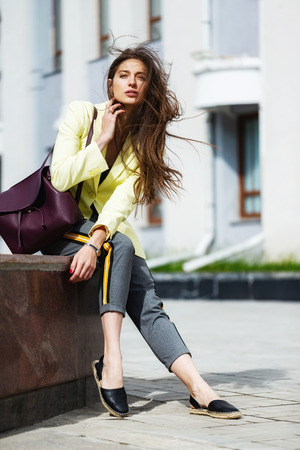 Beautiful female model is sitting outdoors at urban background. Concept of street fashion. Фото со стока