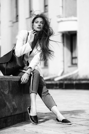 Black and white portrait of beautiful female model is sitting outdoors at urban background. Concept of street fashion.