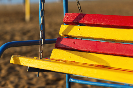 Closeup wooden colorful swing bench at beach background.