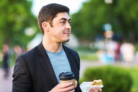 Closeup portrait of smiling elegant man holding pastry and coffee outdoors at green park background. Фото со стока